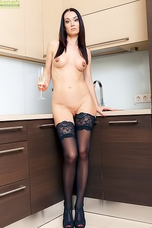 Brunette MILF with black stockings getting drunk while getting naked
