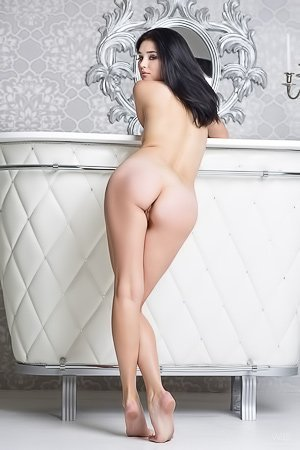 Dark-haired seductress posing totally naked on her white throne