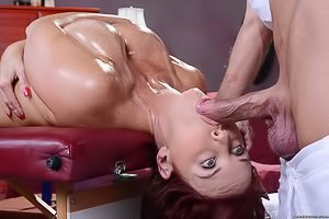 Redheaded, toned and tanned MILF gets oiled-up & fucked by a masseur