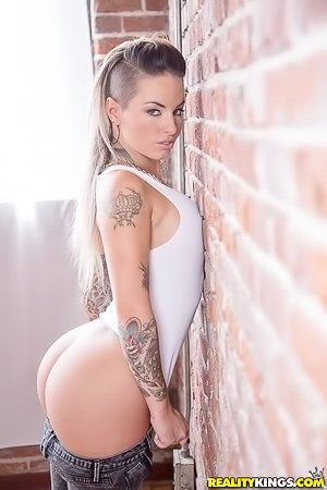 Tatted-up and trashy chick in a white onesie gets destroyed on camera