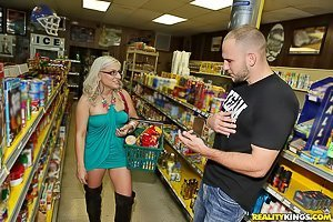 Glasses-wearing blonde in a black thong rides cock in a store